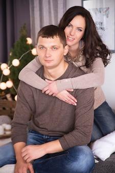 Het mooie jonge paar ontspannen in een woonkamer met nieuwe jaarboom