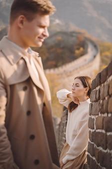 Het mooie jonge paar stellen bij de grote muur van china