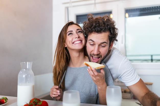 Het mooie jonge paar voedt elkaar en glimlacht terwijl thuis het koken in keuken. het gelukkige sportieve paar bereidt gezond voedsel op lichte keuken voor. gezonde voeding concept.