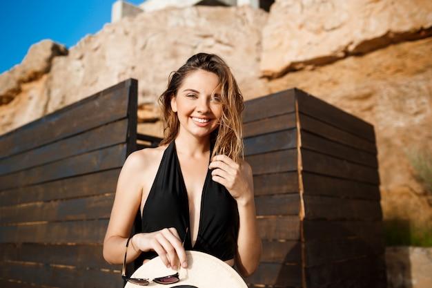 Het mooie jonge vrolijke meisje gekleed in swimwear rust op strand
