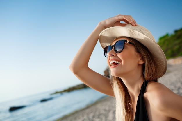 Het mooie jonge vrolijke meisje in hoed en zonnebril rust bij ochtendstrand