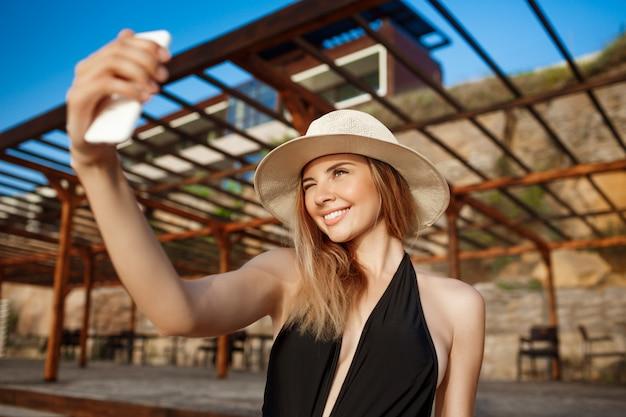 Het mooie jonge vrolijke meisje in hoed rust bij ochtendstrand en maakt selfie
