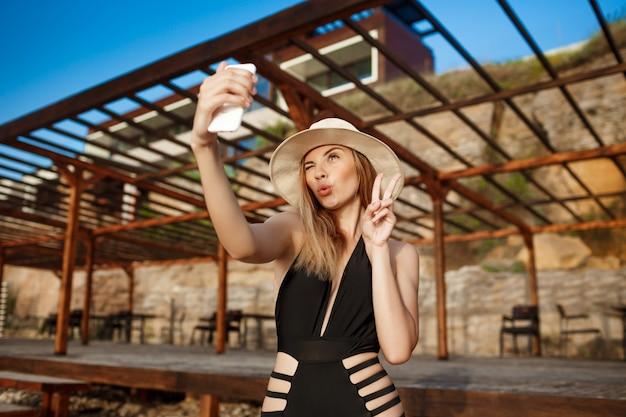 Het mooie jonge vrolijke meisje rust bij ochtendstrand die selfie maken
