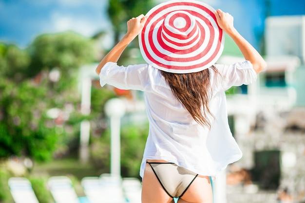 Het mooie jonge vrouw ontspannen aan de rand van infiniti zwembad. achteraanzicht van meisje in bikini en grote rode hoed