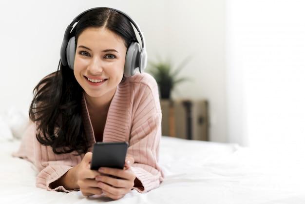 Het mooie jonge vrouw ontspannen die thuis aan muziek met hoofdtelefoons op bed luisteren