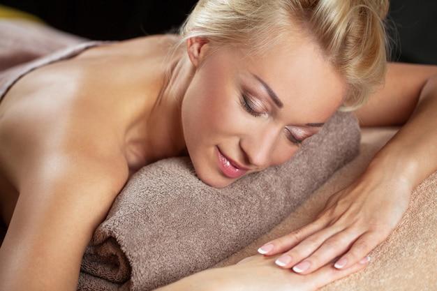 Het mooie jonge vrouw ontspannen in een kuuroord