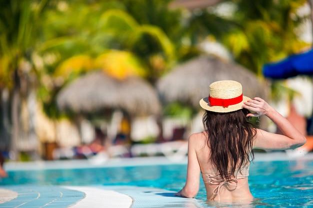 Het mooie jonge vrouw ontspannen in zwembad. achteraanzicht van meisje in buitenzwembad in luxehotel