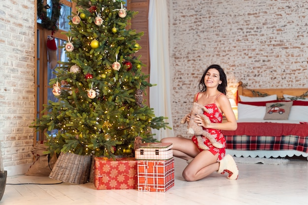 Het mooie jonge vrouw spelen met een teddybeer door de kerstboom