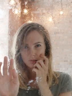Het mooie jonge vrouw stellen achter nat venster