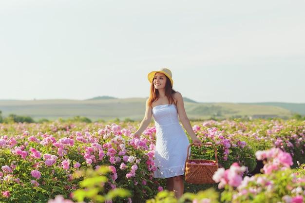 Het mooie jonge vrouw stellen dichtbij rozen in een tuin,