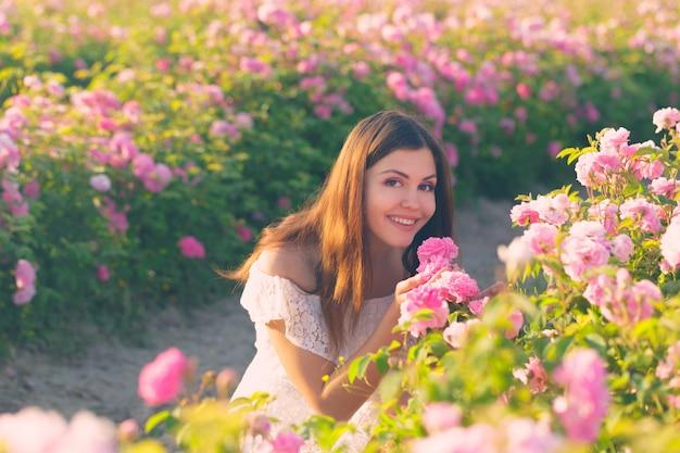 Het mooie jonge vrouw stellen dichtbij rozen in een tuin.