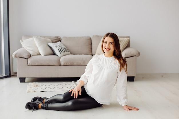 Het mooie jonge zwangere vrouw stellen in kleding