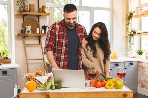 Het mooie jongelui die gelukkig paar glimlachen spreekt en glimlacht terwijl thuis het koken van gezond voedsel met laptop in keuken.
