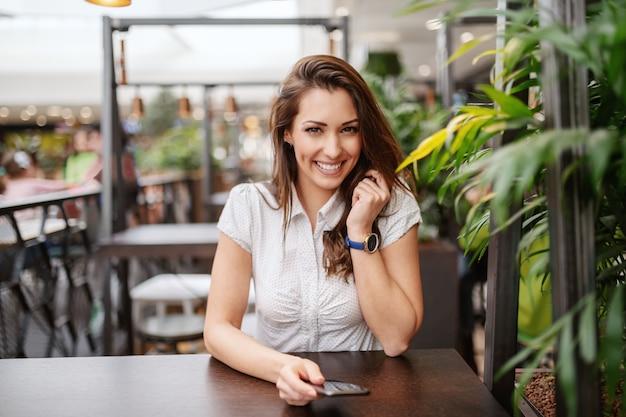 Het mooie kaukasische het glimlachen donkerbruine stellen bij koffiewinkel terwijl het houden van slimme telefoon.