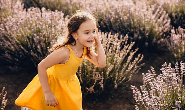 Het mooie kaukasische meisje dat een gele kleding draagt, speelt vreugdevol met haar haar in een lavendelgebied