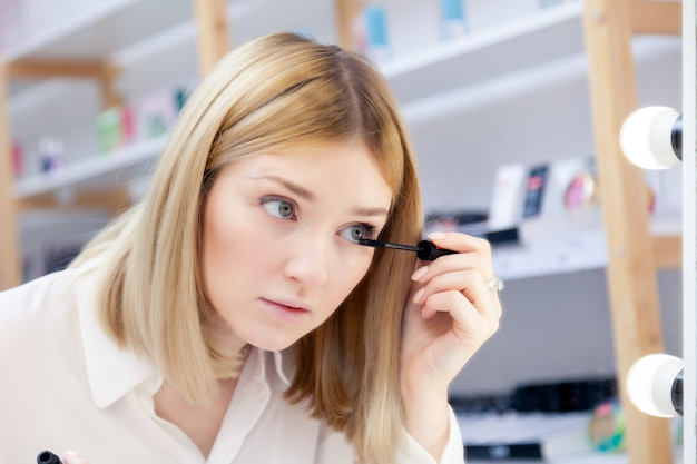 Het mooie kaukasische meisje maakt omhoog kunstenaar, visagiste, model bekijkt bezinning in spiegel met lampen en het toepassen van zwarte zweepmascara. advertentie geen merk decoratieve professionele cosmetische winkel