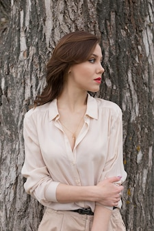 Het mooie kaukasische meisje met rode lippen in modieuze beige blouse kijkt zorgvuldig opzij. eenzaamheid concept