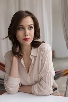 Het mooie kaukasische meisje met rode lippen in modieuze beige blouse kijkt zorgvuldig opzij, leunend op lijst in koffie.