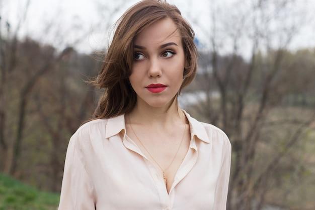 Het mooie kaukasische meisje met rode lippen, krullend haar in modieuze beige blouse kijkt zorgvuldig opzij. eenzaamheid concept