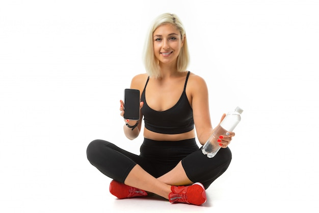 Het mooie kaukasische meisje van de sport zit op vloer, dwarsbenen, toont een mobiele telefoon en houdt een fles water geïsoleerd
