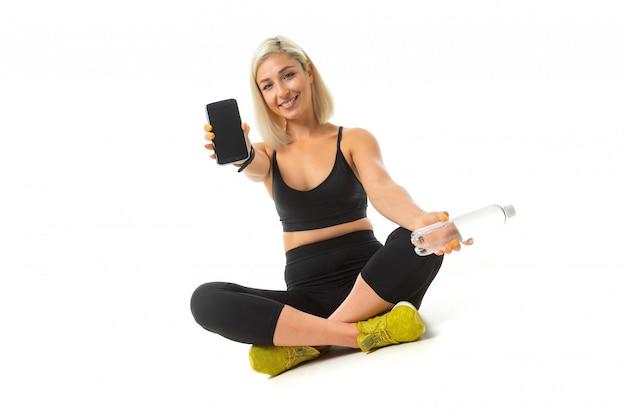 Het mooie kaukasische meisje van de sport zit op vloer in gele tennisschoenen, dwarsbenen, toont een mobiele telefoon en houdt een fles water geïsoleerd