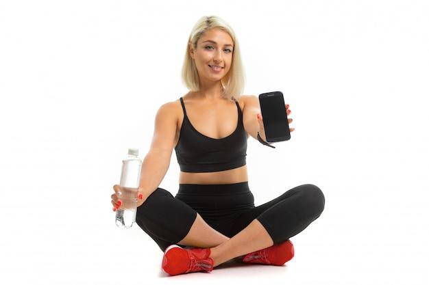 Het mooie kaukasische meisje van de sport zit op vloer in onderzoekstennisschoenen, dwarsbenen, toont een mobiele telefoon en houdt een fles water geïsoleerd