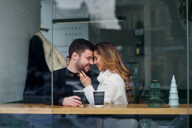 Het mooie kaukasische paar in liefde drinkt koffie bij koffie. liefde en romantisch.