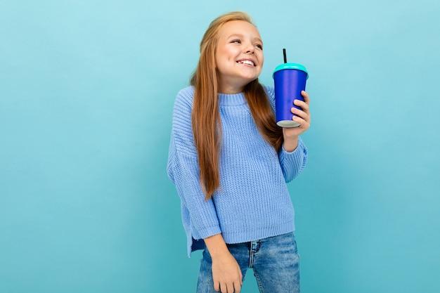 Het mooie kaukasische tienermeisje met bruin haar in blauwe hoody drinkt koffie met blauwe kop die op blauw wordt geïsoleerd