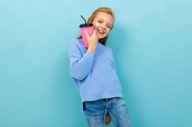 Het mooie kaukasische tienermeisje met bruin haar in blauwe hoody drinkt koffie met roze die kop op blauw wordt geïsoleerd