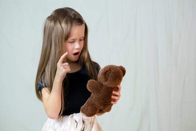 Het mooie kindmeisje spelen met haar teddybeerstuk speelgoed.