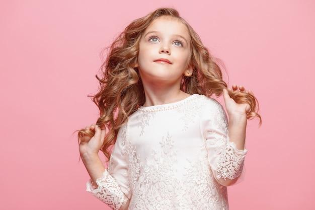 Het mooie kleine meisje in lange jurk staat en poseert over roze achtergrond