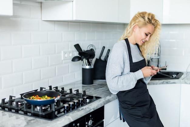 Het mooie kokende voedsel van het blondemeisje in pan, gebruik op de mobiele telefoon en glimlachend terwijl thuis het koken in keuken