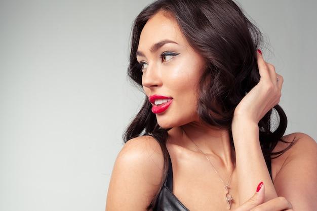 Het mooie lange portret van de haar jonge vrouw met make-up, studio