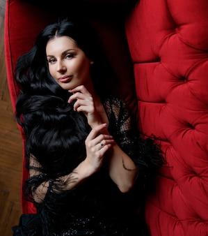Het mooie langharige donkerbruine kaukasische meisje kijkt recht en ligt op de rode bank