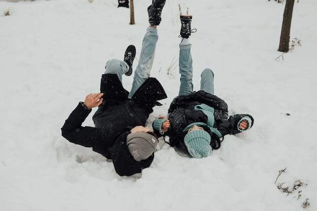 Het mooie liefdevolle gelukkige paar ligt in de sneeuw in de winterpark