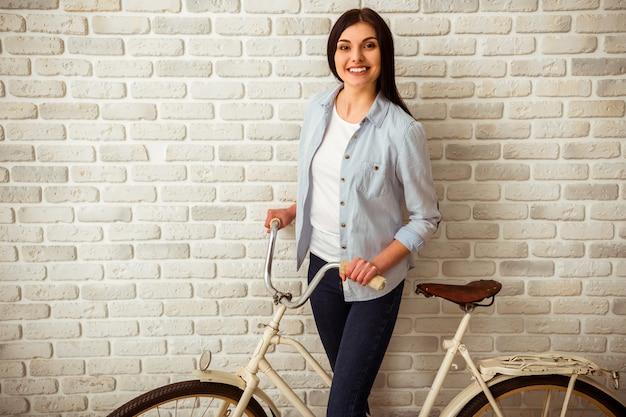 Het mooie meisje bevindt zich dichtbij de witte muur met een fiets.