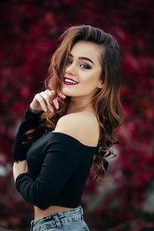 Het mooie meisje bevindt zich dichtbij walll met bladeren