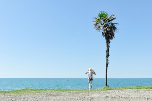 Het mooie meisje bevindt zich met haar rug op een achtergrond van hoge palm, overzees en blauwe hemel