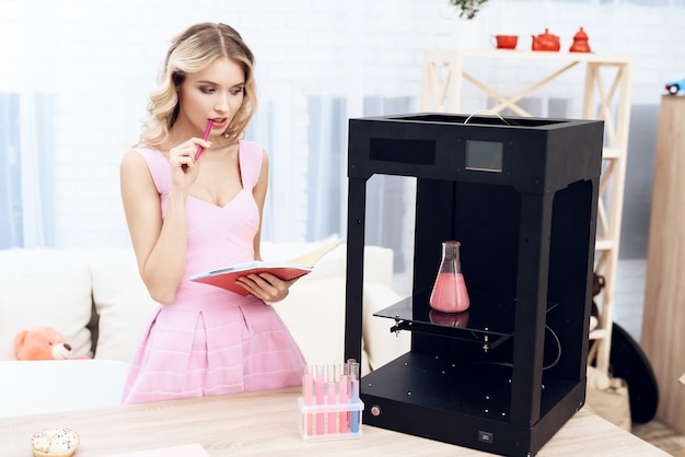 Het mooie meisje creëerde een fles met vloeistof in een 3d-printer.