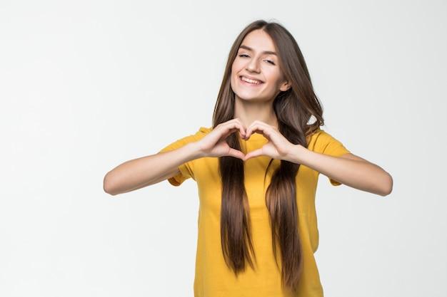 Het mooie meisje dat een hartsymbool met haar maakt overhandigt haar hart dat op witte muur wordt geïsoleerd