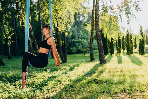 Het mooie meisje dat vliegyoga in het zitten doet stelt in openlucht bekijkend de camera