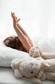 Het mooie meisje die haar handen in een wit bed met konijnenspeelgoed uitrekken dat dichtbij ligt