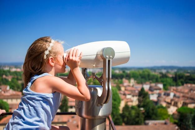 Het mooie meisje die in werking gesteld muntstuk verrekijker op terras bekijken bij kleine stad in toscanië, italië