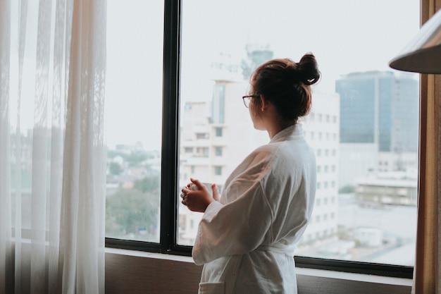 Het mooie meisje drinkt een kop van koffie in de ochtend bij hotel