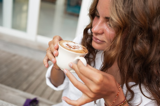 Het mooie meisje drinkt koffie.