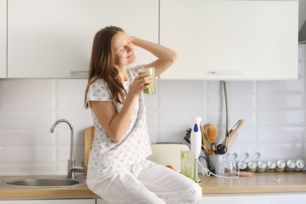 Het mooie meisje drinkt vers bereide smoothie in keuken. smoothies vers gemaakt van diverse plantaardige ingrediënten op aanrecht. gezond eten. selectieve aandacht