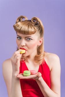 Het mooie meisje eet kleurrijke makaron. sexy vrouw eet franse bitterkoekjes. dieet concept. zoet eten.