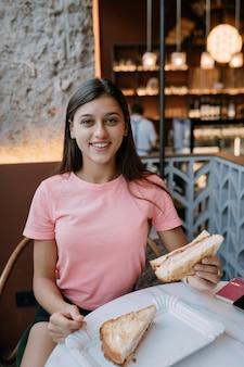 Het mooie meisje eet sandwich