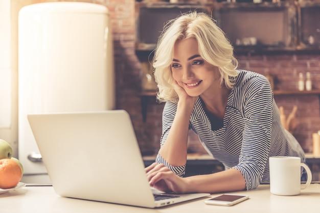 Het mooie meisje gebruikt laptop en het glimlachen