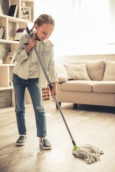 Het mooie meisje gebruikt zwabber en glimlacht terwijl het schoonmaken van huis.